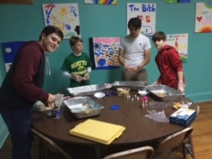 MACC youth decorate cookies to be handed out at weekly community meal.